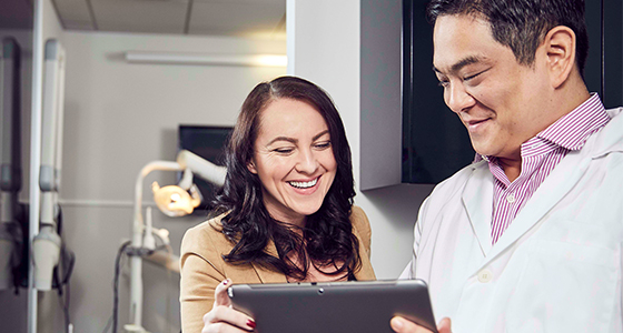 Woman and dentist looking at tablet