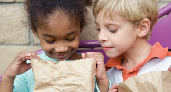 Kids looking at paper bag lunch
