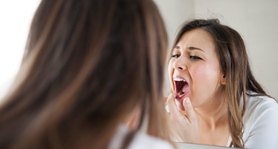 Woman examines tooth in mirror