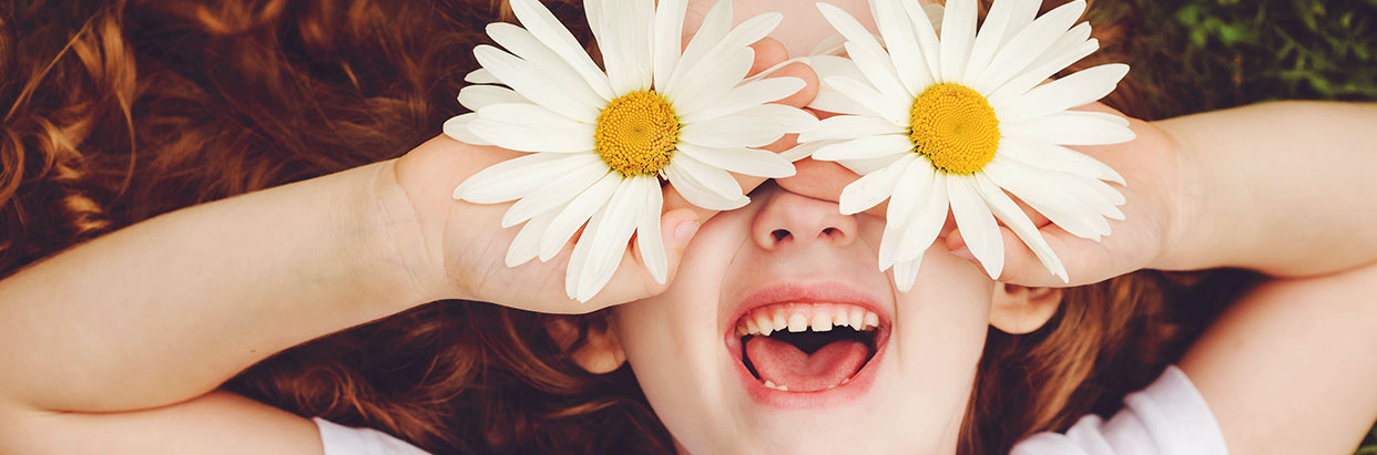 Young girl with flowers over eyes