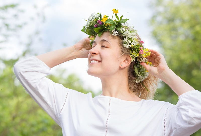 Beautiful young blond woman with flower  wreath on the meadow on a warm summer day. Smiling girl with wild flowers wreath enjoying sun outdoors. Happy woman in the garden. Lifestyle, summer concept
