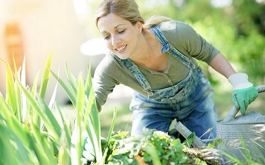 Smiling blond woman gardening