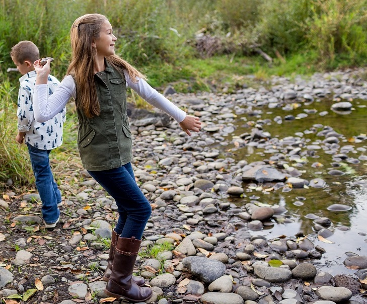 Siblings Throwing Rocks In River Together
