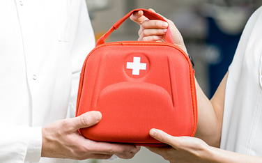 Pharmacist with client and first aid kit in the pharmacy