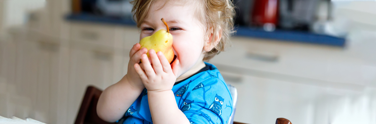 Boy biting into pear
