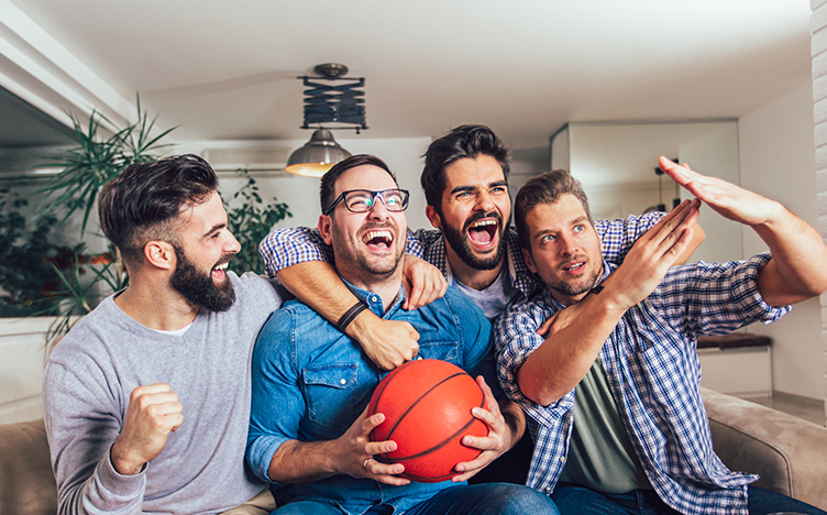 Group of friends cheering for a game of sports on television.