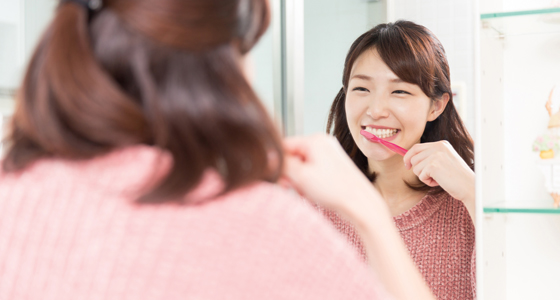 Woman brushing teeth in mirror