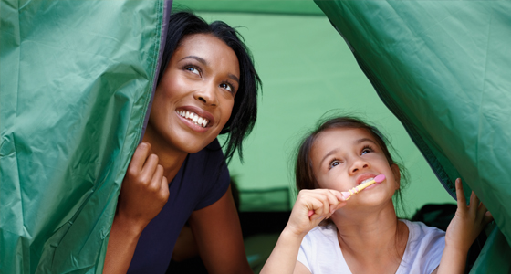 Girl brushing teeth in tent