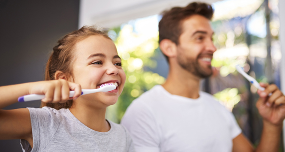 Girl brushing teeth with dad